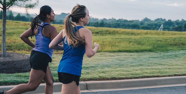 Two girls in athletic wear run along the side of the road.