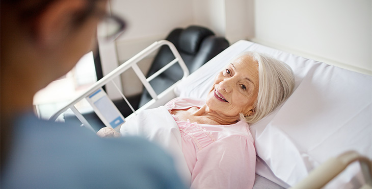 Senior woman smiling at female nurse in hospital