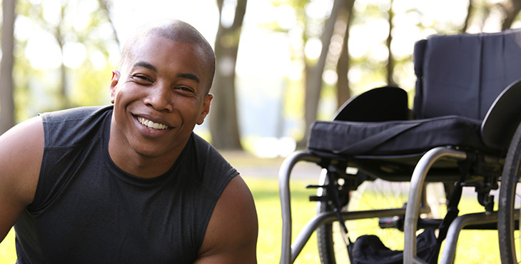 A closeup shot of man in the park is smiling at the camera in the forefront with a wheel chair in the background.