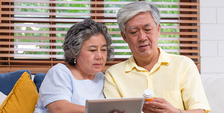 Asian senior couple use tablet searching prescription of pill while sitting on sofa at home,senior learn to use technology.aging at home