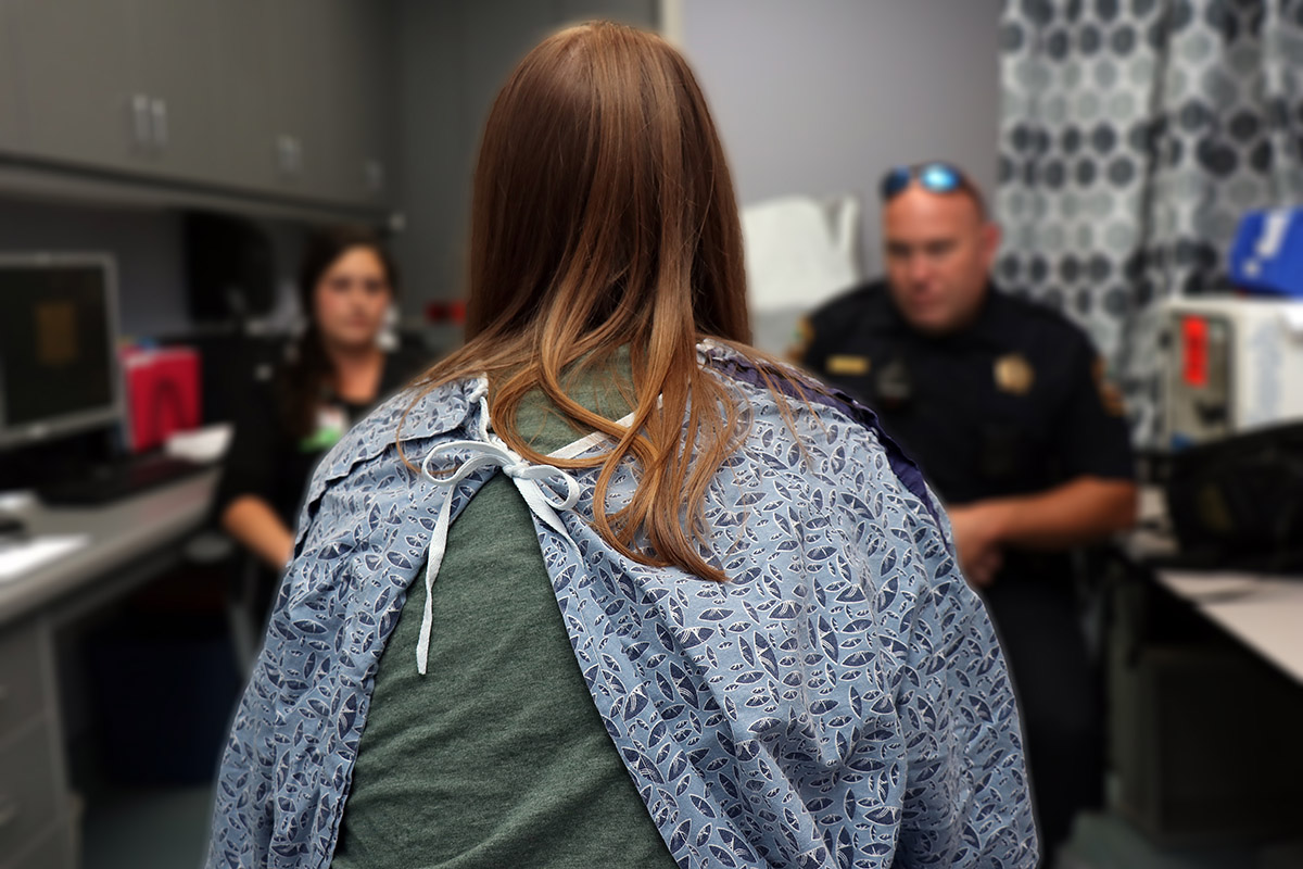 An unidentifiable sexual trafficking victim sits with her back to the camera and discusses the aftermath assault with members of law enforcement