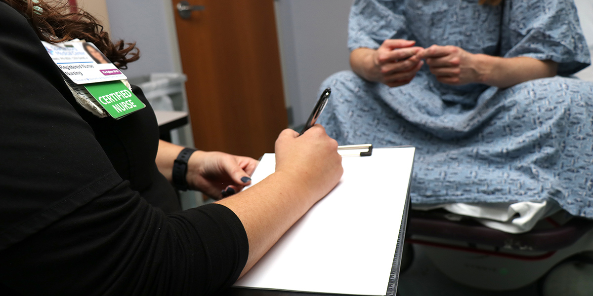 The lower half of an unidentifiable patient is shown wearing a hospital gown and sitting on a table in a hospital room waiting to be examined by a sexual assault nurse examiner (sane)
